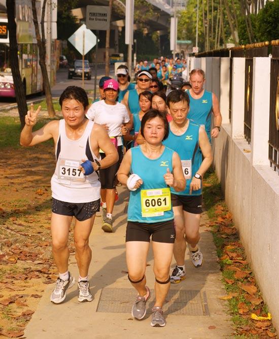String of runners throng the walk path along Telok Blangah Road