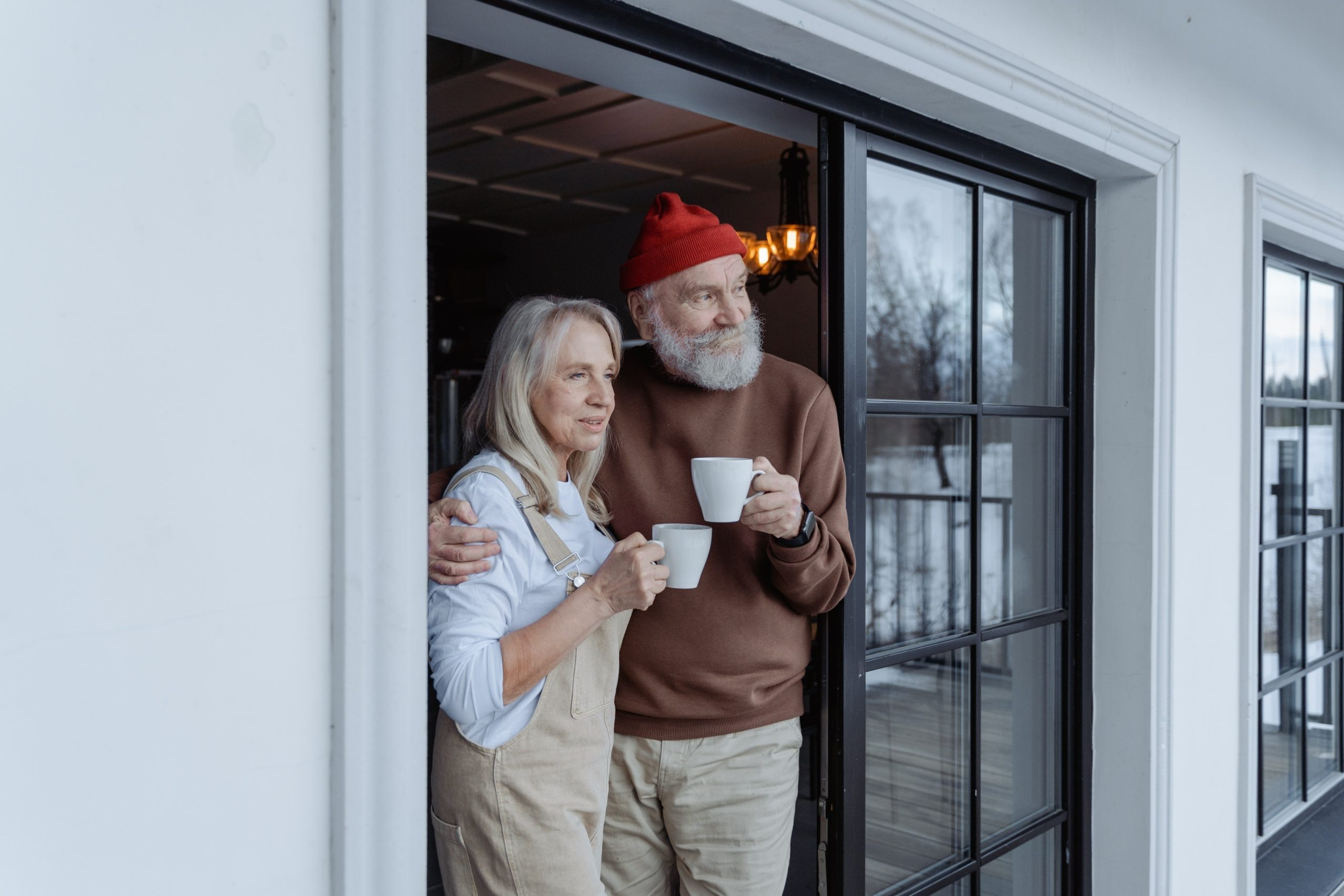 elderly couple looking out their door holding coffee cups - social security cost of living adjustment