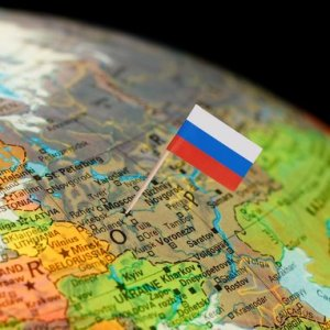 Map with miniature Flag of Russia. Selective focus on Russian