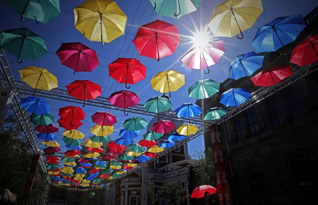 epa04749891 A general view showing the art installation 'Alley of Flying Umbrellas' in central St. Petersburg, Russia, 15 May 2015. Art installation inspired by 'Umbrella Sky Project' of Portuguese town of Agueda and was made of 500 colored umbrellas.  EPA/ANATOLY MALTSEV