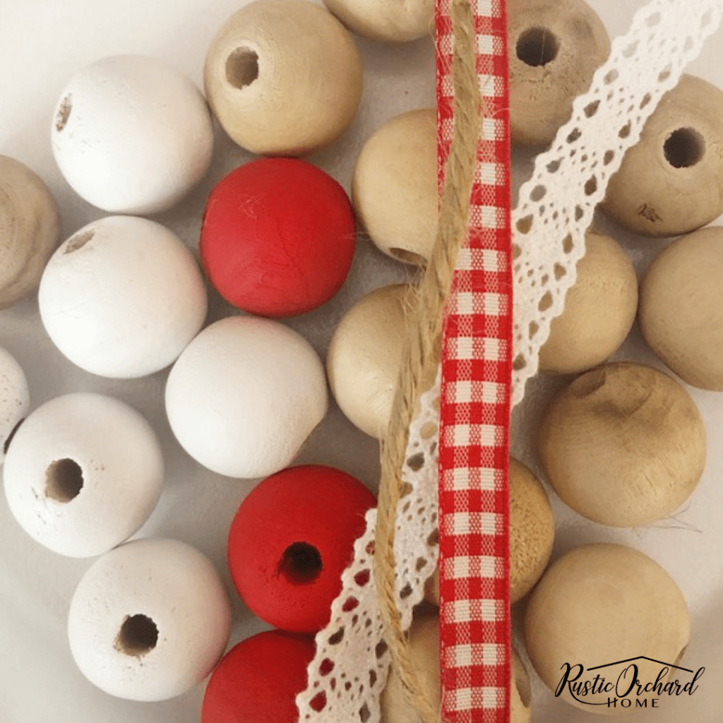Thie DIY Wood Bead Garland is a simple way to dress up your farmhouse home decor on a budget! #rusticorchardhome #woodbeadgarland #diyfarmhousehomedecor #farmhousedecoronabudget #redandwhitedecorideas