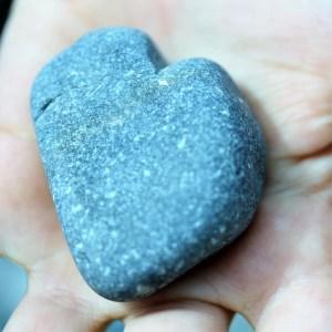 Een steen in de vorm van een hart in een kinderhand. Staat symbool voor een gelukkig kind.