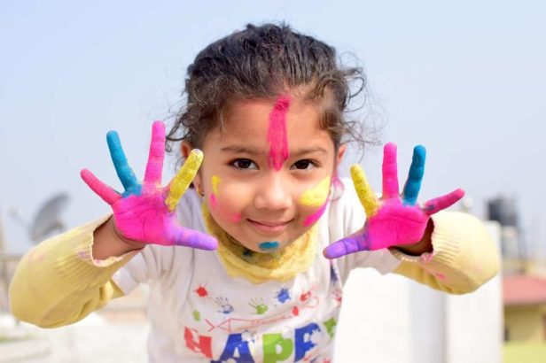 Hands with paint being held up by young girl