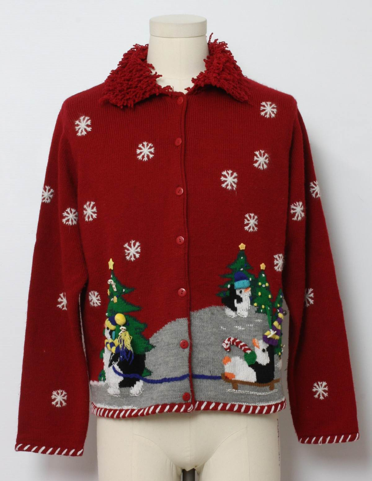 80s style -Karen Scott- Womens Red background cotton ramie blend button front longsleeve Ugly Christmas Sweater, foldover collar with Christmas trees with penguins ice skating. One has a jingle bell from his hat.Candy cane buttons. Snowflakes. Plain red on back. Loose button could be easily repaired, otherwise in good condition