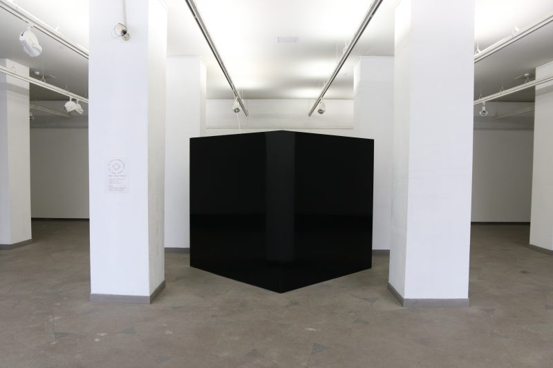 black reflective plexiglass cube in gallery space