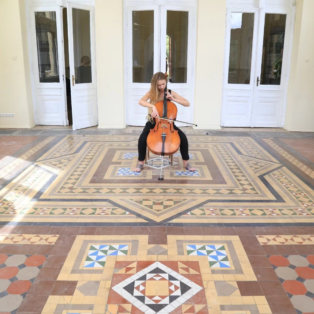 young female artist performing with the cello in orangerie