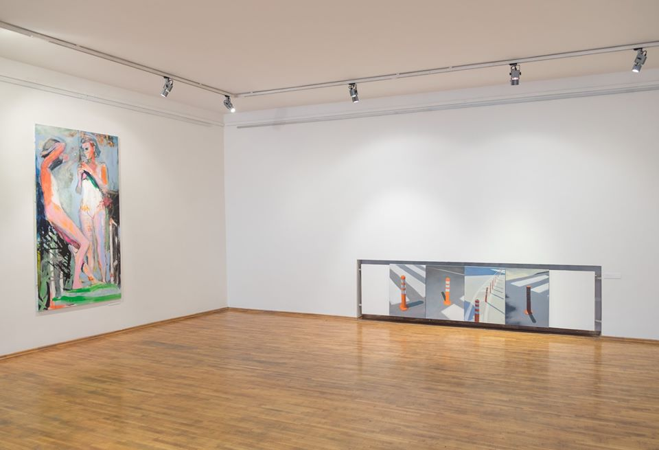 painting exhibition, gallery room, four paintings of road cones by the floor, figurative painting on the facing wall