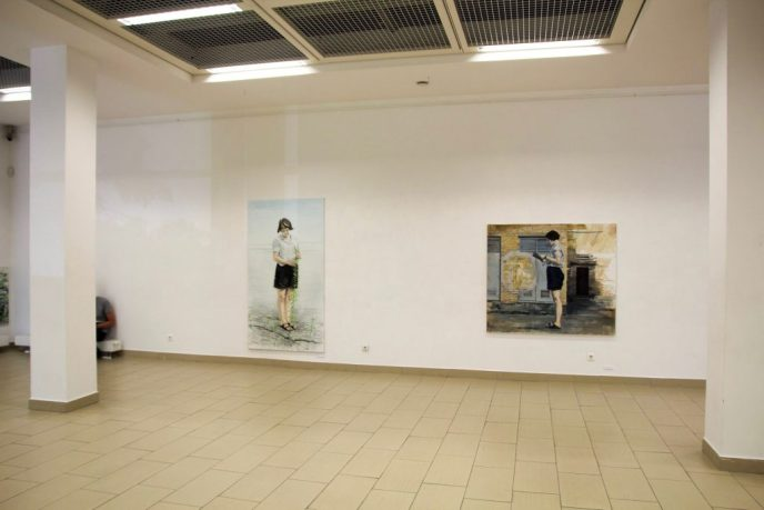 exhibition space, figurative paintings in an exhibition hall. woman holding a plant. reading woman