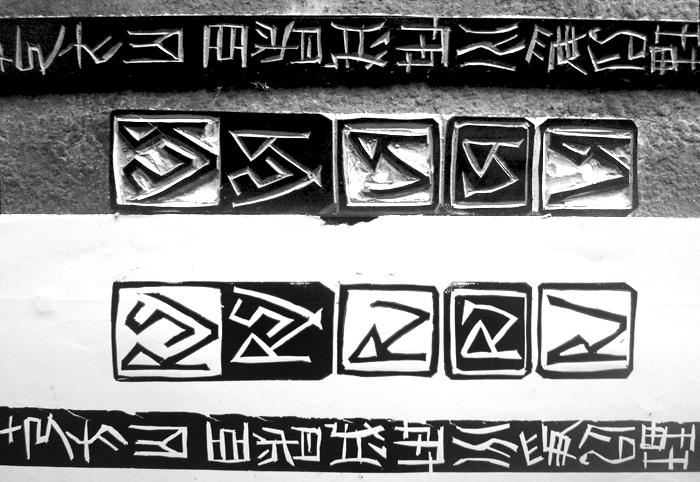 print of characters cut into linoleum and the linoleum block
