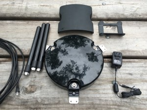 The components of the Winegard ConnecT kit. The large frisbee is the roof unit that the three antennas attach to. The small box above is the indoor router.