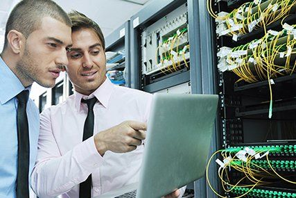 Two IT professionals standing and looking at a computer in front of IT infrastructure