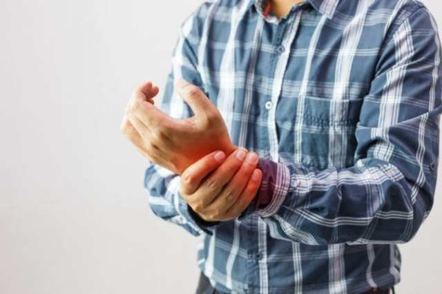 Man Clutching Wrist in Arthritic Pain