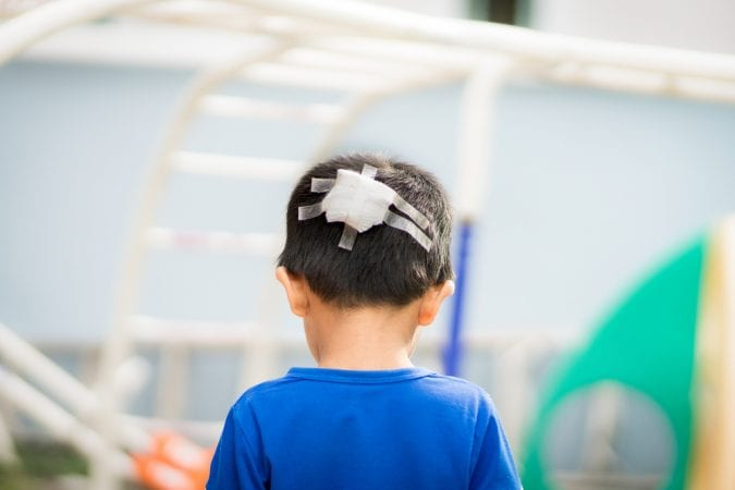 Young Boy Facing Away from Camera with bandage on back of head