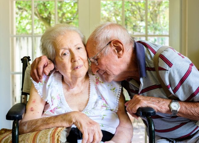 Old Woman with dementia being embraced by her husband