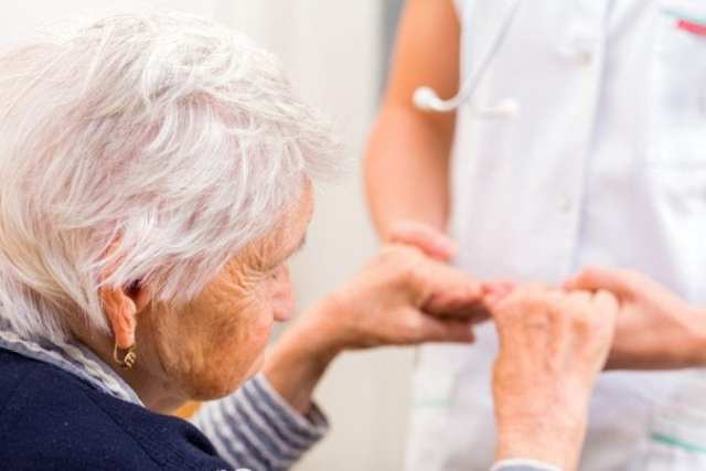 Old Woman getting help to stand up close up on hands
