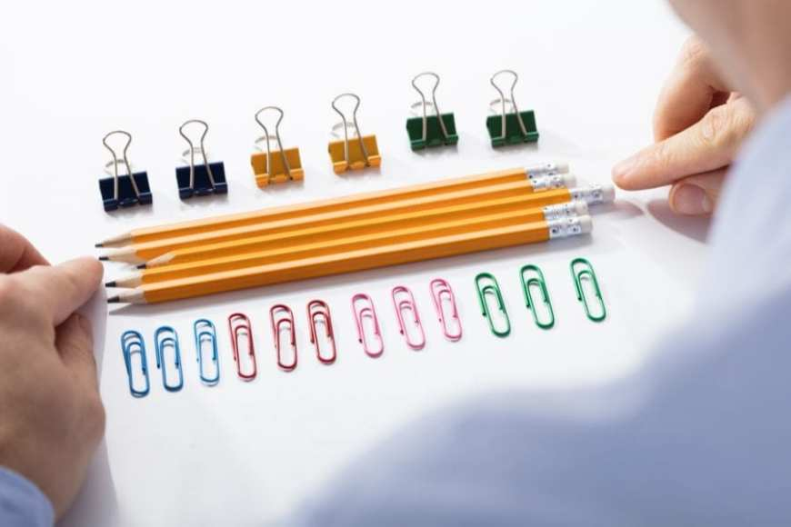 Hands lining up pencils and paperclips