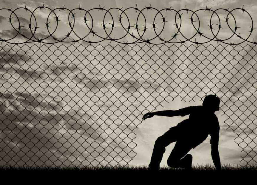 Young boy slipping under barbed wire fence