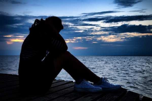 Depressed Woman sitting at water