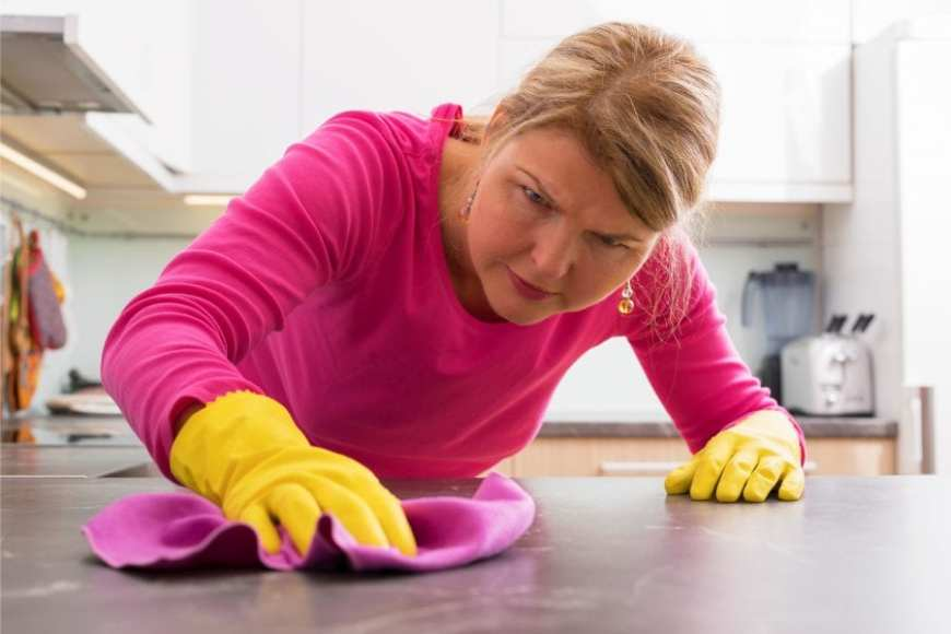 Woman scrubbing her kitchen counter OCD