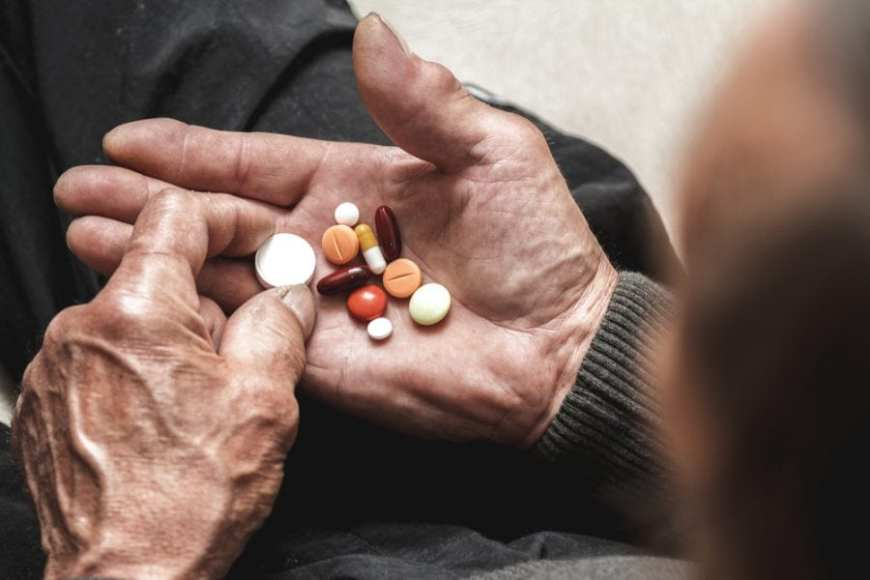 Elder hands of man counting out prescription pills