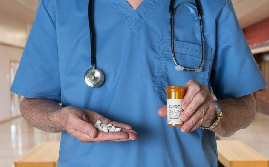 torso of doctor close up holding out prescription pain meds