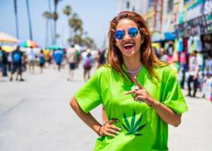 Woman in green cannabis shirt smiling on Venice Beach to help represent the question of can you overdose on weed