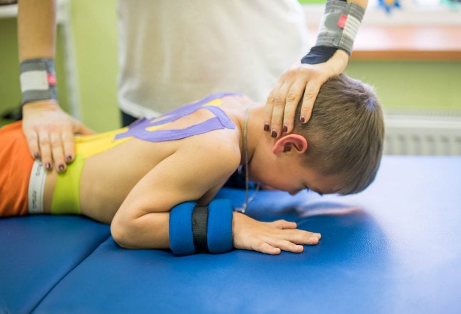 Boy with cerebral palsy in physiotherapy