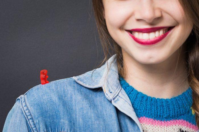 girl smiling with gummy bear on shoulder