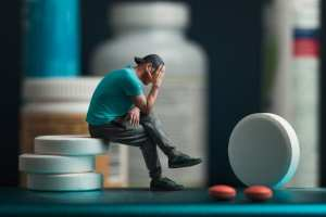 man with head on hands due to pill shaming