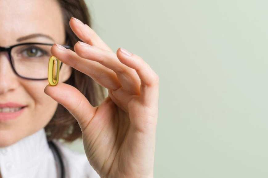 Woman close up holding up CBD capsule