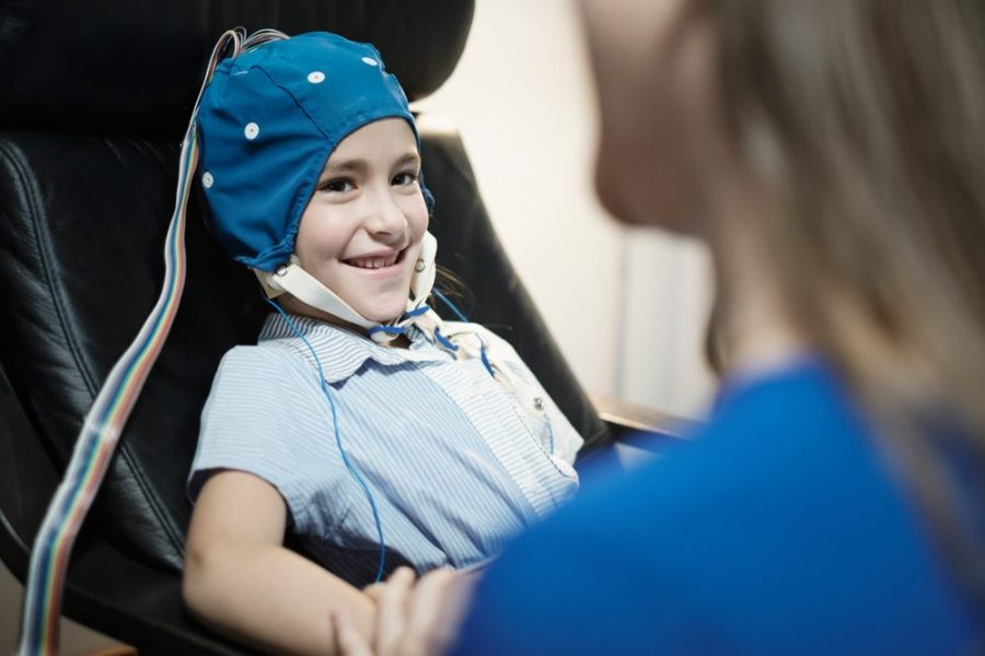 Young teen girl undergoing EEG test holding mother's hand