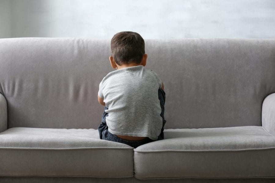 Small Autistic Boy With Back to Camera Sitting on a Couch