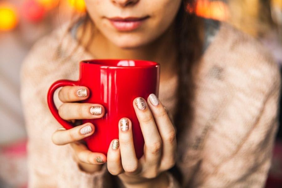 young woman holding red mug with cannabis hot toddy in it