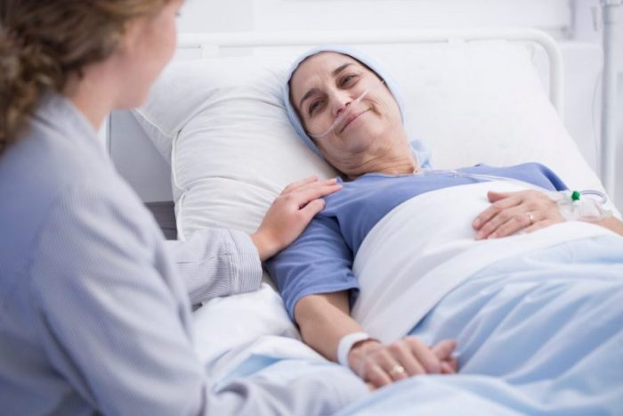 Woman holding the hand of female cancer patient in hospital bed.