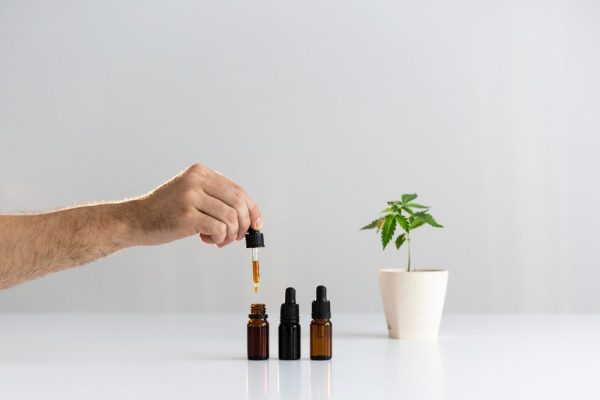 person holding dropper of cannabis oil