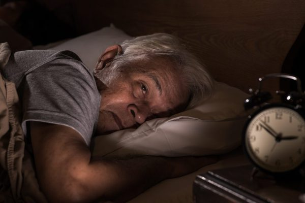 older adult with bad insomnia tries to fall asleep