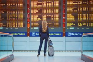 traveling with cannabis represetned by young professional in front of departures board