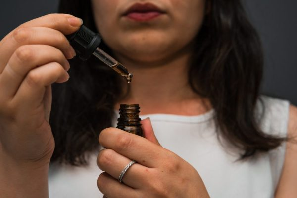 how to use cannabis oil demonstrated by young woman using dropper