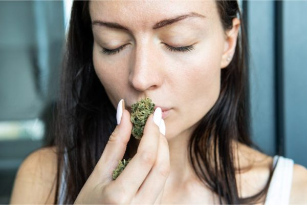 girl smelling weed, probably not odorless