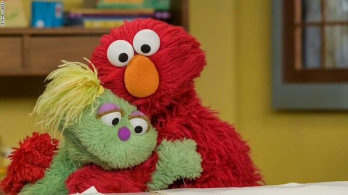 sesame street characters now adress the opioid crisis as elmo gives karli a hug