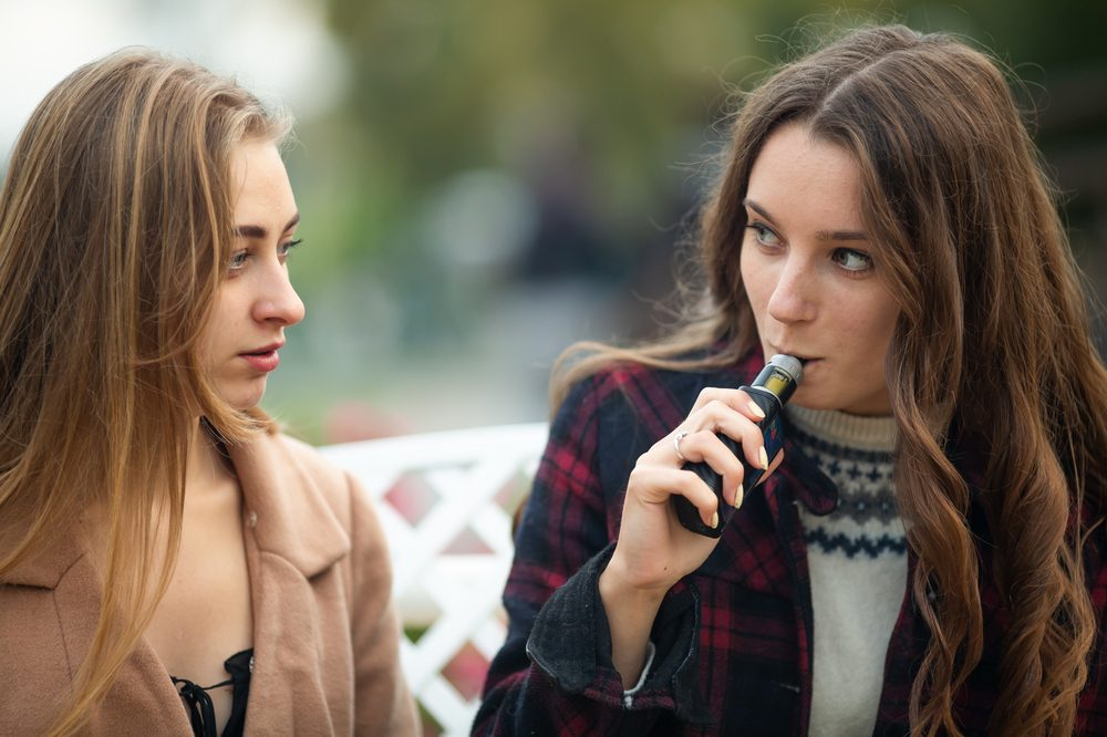 vape illness hinted at by girl staring unsurely at one vaping