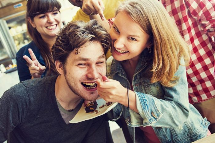 young happy group of people eat brownies