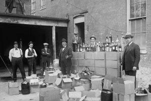 cannabis prohibition looks similar to this old image of alcohol prohibition officers posing in front of confiscated liquor
