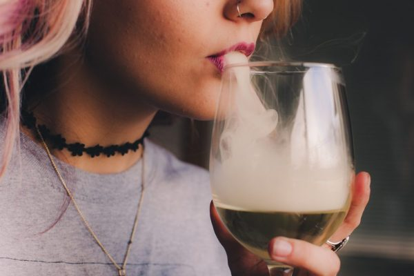 drunk vs high concept represented by woman blowing smoke on wine