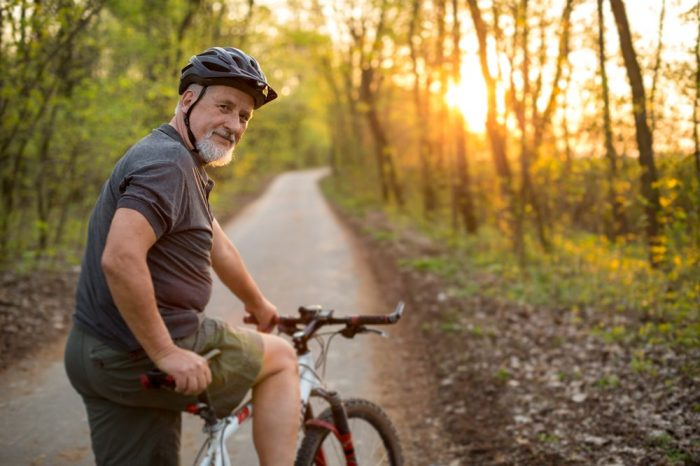 older man no longer living with chronic pain as he rides his bike down a pretty path