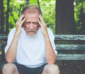 breakthrough pain reliever will help this sad older man with head in hands.