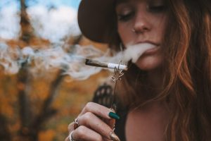 weed tolerance represented by young woman smoking with joint holder shaped like a leaf on a stick
