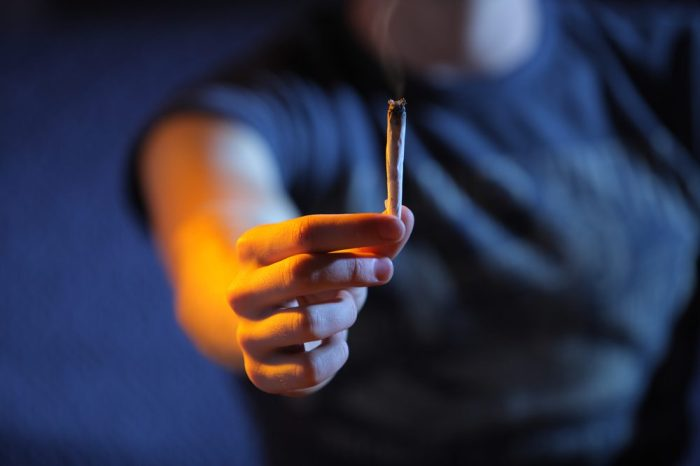 does cannabis lower IQ might be what this hand holding a joint is thinking