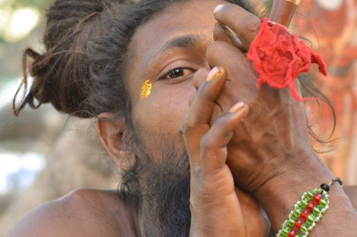 rastafarian like Sadhu smoking out of a Chillum