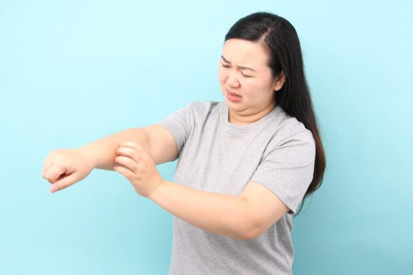 A woman itches her arm. Could a THC slave help with that?